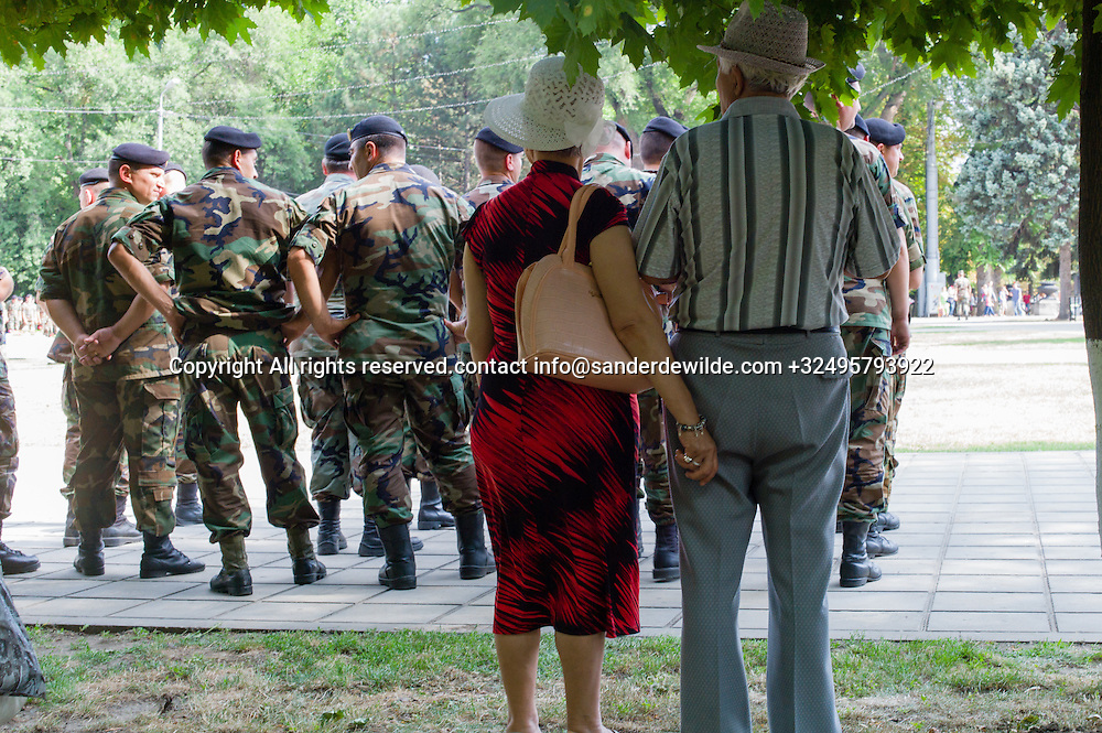 20150824  Moldova Chisinau. Older couple holding hands while watches Soldiers exercise in front of the Victory arc in Chisinau,  for their independance day 27th August. Elite garde with Moldovan national tricolor