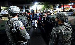 National Guard personnel watch as protesters march down Tyron Street Saturday, September 24, 2016 in Charlotte, NC, USA. Protesters came together for the fifth straight night to protest following the fatal shooting of Keith Lamont Scott. Keith Lamont Scott was shot and killed by Charlotte-Mecklenburg Police Officer Brentley Vinson on Tuesday afternoon. Photo by Jeff Siner/Charlotte Observer/TNS/ABACAPRESS.COM