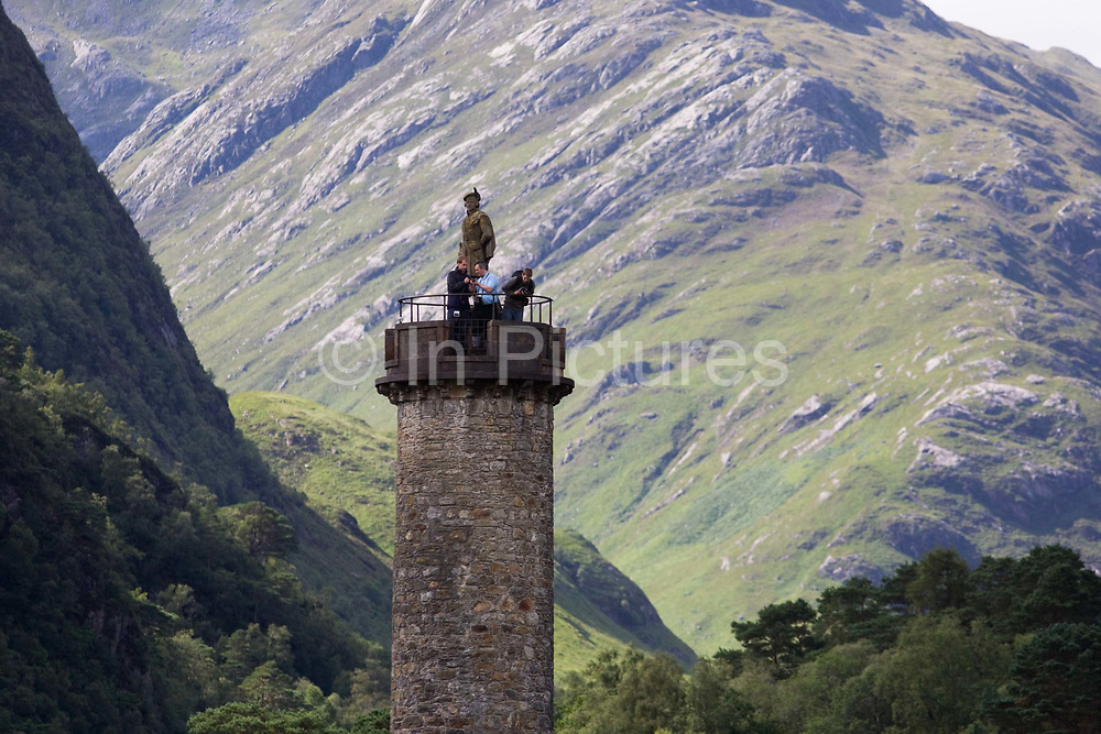 """Looking from a high-viewpoint, we see tourists on top of The Glenfinnan Monument situated at the head of Loch Shiel and erected in 1815 to mark the place where Prince Charles Edward Stuart (""""Bonnie Prince Charlie"""") raised his standard, at the beginning of the 1745 Jacobite Rising. His statue stands on top of the tower just off the A830 road from Fort William to Mallaig. The Jacobite Risings were a series of uprisings, rebellions, and wars in the British Isles occurring between 1688 and 1746. The uprisings were aimed at returning James VII of Scotland and II of England, and later his descendants of the House of Stuart, to the throne after he was deposed by Parliament during the Glorious Revolution."""