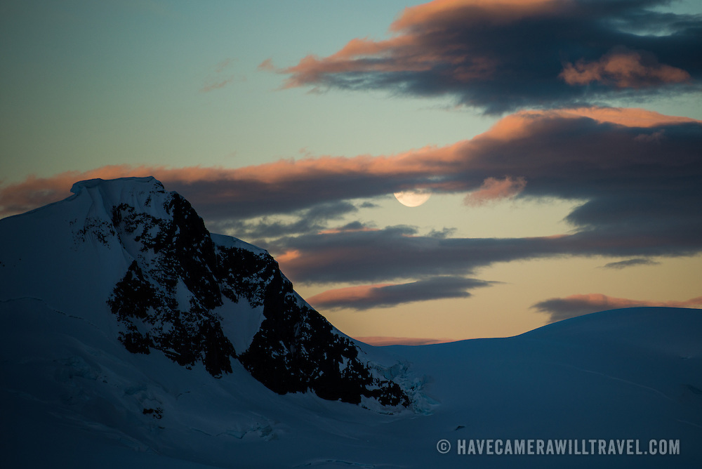 The moon rises over a dramatic snow-covered mountain at Paradise Harbor Antarctica while teh setting sun catches a golden glow on the clouds.