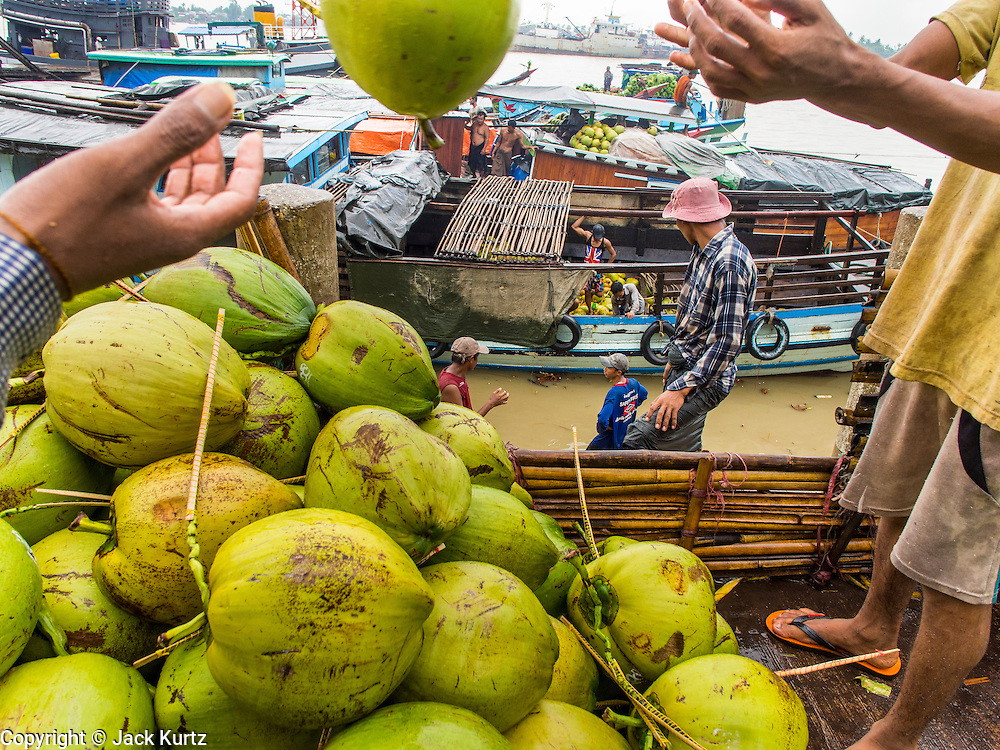 """10 JUNE 2014 - YANGON, MYANMAR:   Porters unload coconuts from a riverboat on the banana jetty. The """"banana jetty"""" is on the Yangon River north of central Yangon on Strand Road. Bananas, coconuts and other fruit are brought in here from upcountry, sold and reshipped to other parts of Myanmar (Burma). All of the labor here is done by hand. Porters carry the produce to the jetty and porters load the boats before they steam upriver.   PHOTO BY JACK KURTZ"""