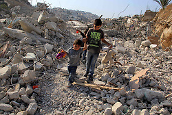 October 26, 2016 - Jerusalem, Jerusalem, Palestinian Territory - Palestinian children walk on the rubbles of their family house that was demolished after Israeli authorities said it was built without a permit in Wadi Qaddum in the East Jerusalem neighborhood of Silwan on Oct. 26, 2016. A multi-unit building belonging to Jaafreh family was demolished leaving an extended family of 30 Palestinians -mostly children- homeless, after the Jerusalem municipality rejected the family's attempts to obtain building permits for nine year  (Credit Image: © Mahfouz Abu Turk/APA Images via ZUMA Wire)