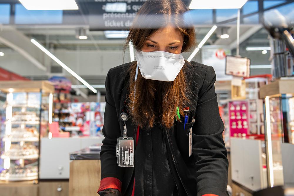 L'Intermarché de La Loupe, le 18 mars 2020<br /> À la caisse centrale, une employée contrôle les nouvelles consignes de sécurité et de protection du personnel.