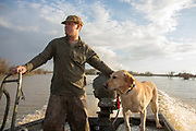 Hunter and Labrador retiever in a duck boat on a shallow marsh.