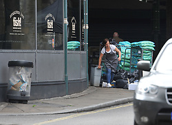 A restaurant worker removes waste from a fish restaurant inside the police cordon at Borough Market following the terror attack in which eight people died.