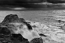 Man standing behind a rock waiting for the sea to calm down. / Maður bíður eftir að veðrinu slotar við Lágey/Dyrhólaey
