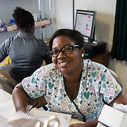 INDIVIDUAL(S) PHOTOGRAPHED: Viola Pierre Louis. LOCATION: Sacré-Cœur Hospital, Milot Commune, Cap-Haïtien, Haïti. CAPTION: Maternity nurse Viola Pierre Louis smiles from behind a desk at Sacré-Cœur Hospital.