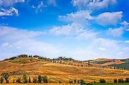 Tuscan hillside with a country house and cypres trees.