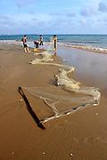 Four men gather up their fishing net on the beach. Mui Ne, Vietnam