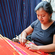 A woman weaving with a traditional backstrap loom in San Antonio Aguas Calientes near Antigua, Guatemala.