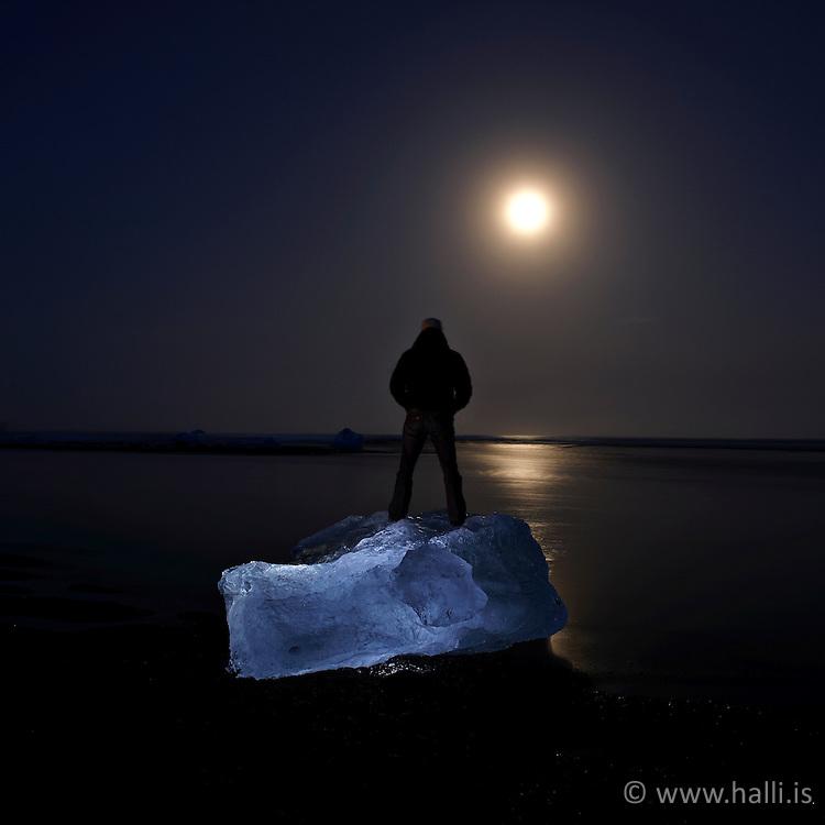 Man standing on a glacier at midnight, Jokulsarlon, Iceland - Maður stendur á ísjaka á miðnætti við Jökulsárlón