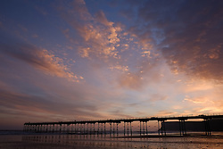 © Licensed to London News Pictures. <br /> 08/10/2014. <br /> <br /> Saltburn, United Kingdom<br /> <br /> The Victorian pier at Saltburn is silhouetted at dawn on Saltburn beach in Cleveland.<br /> <br /> Photo credit : Ian Forsyth/LNP