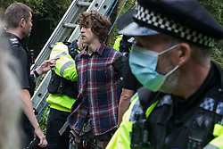 Denham, UK. 24 July, 2020. Police officers arrest Seb, a male activist from HS2 Rebellion, after he had occupied a line above the river Colne attached to an ancient alder tree which he was trying to protect from destruction in connection with works for the HS2 high-speed rail link in Denham Country Park. A large policing operation involving the Metropolitan Police, Thames Valley Police, City of London Police and Hampshire Police as well as the National Eviction Team was put in place to enable HS2 to remove the tree.