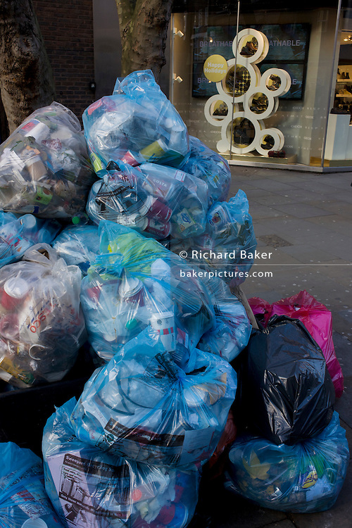Piles of rubbish bags awaiting collection by council refuse collectors in Covent Garden, central London.