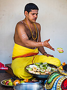 27 DECEMBER 2015 - SINGAPORE, SINGAPORE: A Hindu priest performs a religious ritual at the Sri Mariamman temple in Singapore. The Sri Mariamman Temple is Singapore's oldest Hindu temple. It is an agamic temple, built in the Dravidian style. The temple is in the downtown Chinatown district, and serves Hindu Singaporeans and Tamilians. Due to its architectural and historical significance, the temple has been gazetted a National Monument and is a major tourist attraction. The Sri Mariamman Temple was founded in 1827 by Naraina Pillai, eight years after the East India Company established a trading settlement in Singapore.       PHOTO BY JACK KURTZ