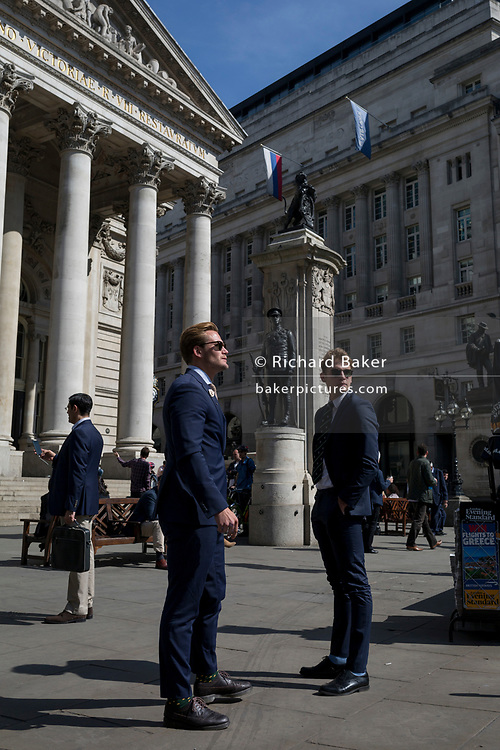 Young men below the classical architecture of Royal Exchange and the WW1 war memorial at Bank Triangle, on 10th May 2017, in the City of London, England.
