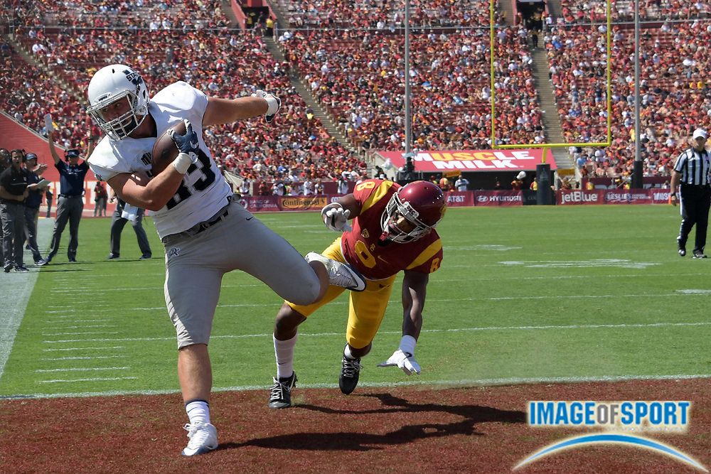 Sep 10, 2016; Los Angeles, CA, USA; Utah State Aggies tight end Wyatt Houston (83) is defended by USC Trojans defensive back Iman Marshall (8) on a 6-yard touchdown reception during a NCAA football game at Los Angeles Memorial Coliseum. USC defeated Utah State 45-7.