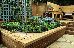 Brick raised bed topped with sleepers in the vegetable area