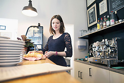 Young woman working in coffee shop serving croissant, Freiburg Im Breisgau, Baden-Wuerttemberg, Germany