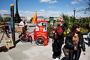 Spring community activities on The Southbank, London. British seaside in central London, on a 70-metre beach that appears on Queen's Walk for the duration of the Festival of Britain celebrations. Popcorn seller