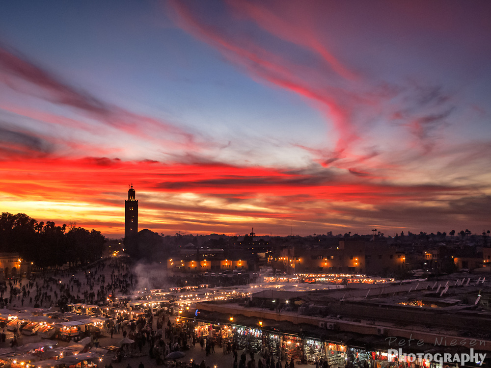 Marrakesh Cityscape view of dramatic red ribbon clouds and sunset with minaret tower and night market