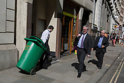 A worker pulls a green wheelie bin past suited businessmen in the City of London, the capital's financial district aka the Square Mile, on 17th May 2018, in London, UK.