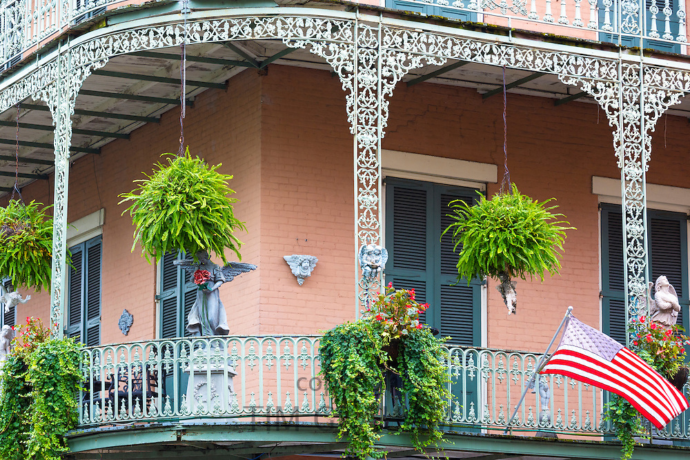 Bright architecture wrought iron balcony and flag on corner St Philip and Royal Street in French Quarter, New Orleans, USA