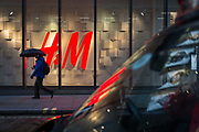 A pedestrian under an umbrella walks past the H&M logo, on 28th February 2017, in the City of London, England.