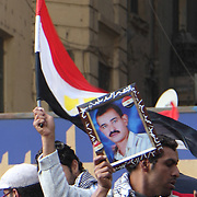 A young Egyptian man waves the photograph of his relative, a victim of the Mubarak regime, and calls for justice.