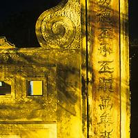 Asia, Vietnam, Hoi An, Street lights illuminate temple gates at night along Thu Bon River