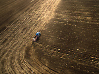 Aerial view of farmer plowing in a farm in the countryside.