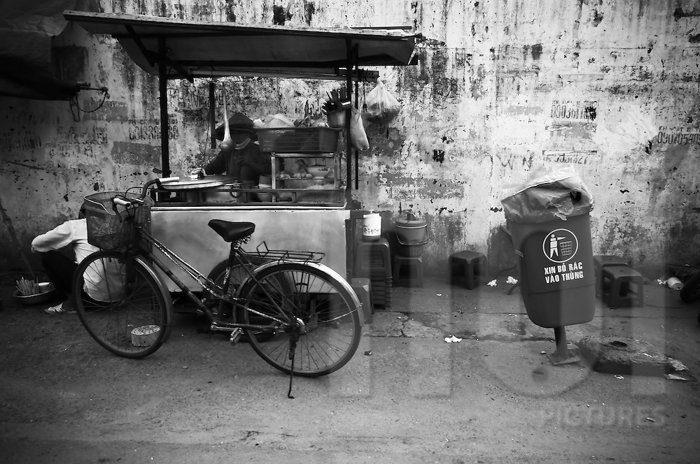 A woman is preparing her street food stand in front of a dirty wall. Ho Chi Minh city, Vietnam, Asia