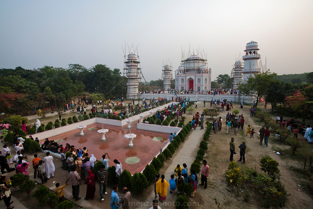 Tourists stand outside the Taj Mahal Bangladesh, a replica of India's famed Taj Mahal erected by Ahsanullah Moni, a millionaire film director and businessman. The Bangla Taj sits in the middle of rice fields near Moni's home village outside of Dhaka, Bangladesh. He says he built it because most  Bangladeshi people cannot afford the trip to Agra, India to see the real thing. The entry fee for his replica is 50 Taka, about  0.75 USD. There is a 25-room hotel facing the Bangla Taj and he says his plans include a film studio and center nearby. The construction of the main Taj will be completed in about a month but the tourist attraction is now open to the public. Moni claims about 20,000 people visit daily. There is only a single lane two kilometer road winding through the surrounding rice fields connecting the main road to his attraction, near the town of Sonargaon, about 30 kilometers from Dhaka.