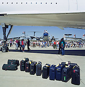 Baggage belonging to a British Airways Concorde crew is lined up beneath their aircraft after arriving at Oshkosh Air Venture, the world?s largest air show in Wisconsin USA. Twelve cases match 12 of Concorde's tiny windows and some of the crowd either take shelter from the sun or walk around the supersonic jet in awe of this engineering marvel. Their baggage is lined up beneath the aircraft during its visit to this huge show in Wisconsin, USA. Close to a million populate the mass fly-in over the week, a pilgrimage worshipping all aspects of flight. The event annually generates $85 million in revenue over a 25 mile radius from Oshkosh. Picture from the 'Plane Pictures' project, a celebration of aviation aesthetics and flying culture, 100 years after the Wright brothers first 12 seconds/120 feet powered flight at Kitty Hawk,1903. .