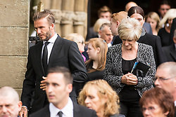© Licensed to London News Pictures. 27/08/2015. Bury, UK.  Picture shows David Beckham with his mother Sandra. The funeral of Neville Neville father of footballers Gary & Phil Neville & England net ball coach Tracey has taken place today at Bury Parish church. Neville died in Australia after being taken ill on a visit to support his daughter  Tracey.  Photo credit: Andrew McCaren/LNP