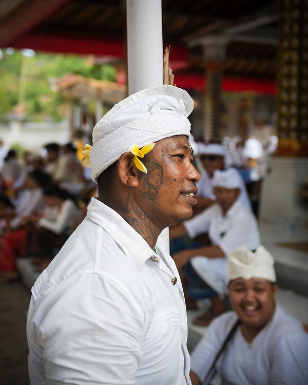 Ped, Nusa Penida, Indonesia - October 5, 2017: The day before Nyepi Laut, a holiday in which the sea is given a rest (no boats, swimming, etc), a man sits in the temple of Pura Dalem Pentaran Ped on the island of Nusa Penida in Indonesia.