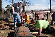 22 FEB. 2017 -- UNIVERSITY CITY, Mo. -- Ron Klump, Nathan Fohne and Spencer Pensoneau, all of Rosenbloom Monument Company, work to lift a headstone displace by vandals at the Chesed Shel Emeth Cemetery in University City, Mo., Feb. 22, 2017. According to cemetery management 154 headstones were knocked over and damaged by vandals during the previous weekend at the 124-year-old Jewish cemetery. An online fundraising project organized by area Muslims to help pay for repairs reached its goal of $20,000 in three hours and has reportedly more than tripled that amount. <br /> <br /> Photo by Sid Hastings.