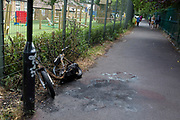 The wreckage of a burned-out scooter leans abandoned against fencing in an alleyway outside a local scool in Beckenham, on 14th June 2020, in London, England.