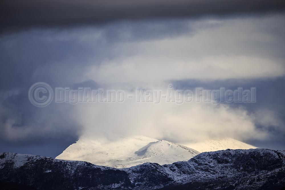 Snowy montain surronded by cloud | Snødekt fjell omkranset av en sky.