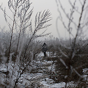 A migrant walks through a frozen field near Belgrade's Ain railway station.