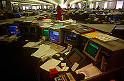 An interior of office desks and 90s computers in the trading floor of The Chemical Bank in the City of London, the capital's financial centre. Screens glow with the most up to date trading figures and news items allowing traders to react instantly on the money markets. Large keyboards and hard drives and deep monitors were state of the art technology in the early 1990s.