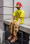 """A carved wooden puppet resembles Pinocchio, on the street of Cortina d'Ampezzo, in the Dolomites, Veneto, Italy, Europe. Pinocchio is a fictional main character of the children's novel """"The Adventures of Pinocchio"""" (1883), by Italian writer Carlo Collodi. Carved by a woodcarver named Geppetto in a small Italian village, he was created as a wooden puppet, but dreamed of becoming a real boy. Pinocchio has a short nose that becomes longer when he is under stress (chapter 3), especially while lying."""