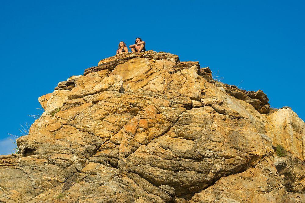 A young couple, from Mexico and France, sit together with eyes closed atop a rocky point on the coast of Mazunte, located in Mexico's Oaxaca State.