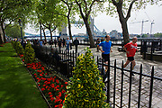 Joggers and the Olympic rings hanging from London's Tower Bridge, weeks before the Olympiad in July 2012. The men run over the old cobbled street alongside the river, lawns and flowerbeds that are beautifully maintained for the thousands of visitors to this iconic London Landmark. The Victorian Tower Bridge (built 1886–1894), a combined bascule and suspension bridge close to the Tower of London, from which it takes its name. The five Olympic rings are suspended from the upper walkway in the weeks before the start of the London 2012 Olympics.