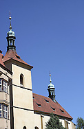 Church Bell Tower in the Jewish part of Prague, clear blue sky and trees in front.