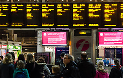 © Licensed to London News Pictures. 22/12/2012. London, UK. Travellers in Paddington Railway Station stand before signs warning of delays to rail services to the South West of England as a result of heavy rain and flooding. Photo credit : Richard Isaac/LNP