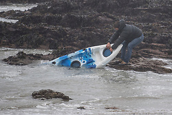 © Licensed to London News Pictures. 02/03/2018. FALMOUTH CORNWALL, UK. Rescuing a canoe washed in by the storm. Storm Emma caused damage to the beaches and businesses of Falmouth at the morning high spring tide today. The strong wind and the spring tide caused a beach to be washed away at Gylly beach. At Swanpool beach the beach was washed onto the road causing it to be blocked .  Photo credit: MARK HEMSWORTH/LNP