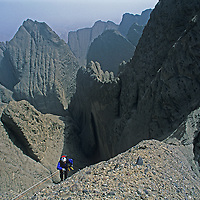 Mountaineer Sam Lightner, Jr. climbs treacherous conglomerate rock on Shipton's Arch in the arid Kara Tagh Mountains next to the hazy Taklimakan Desert near Kashagar (Kashi) in Xinjiang Province, China. Later the expedition crossed the range by descending the dangerous and unexplored slot canyon below him.