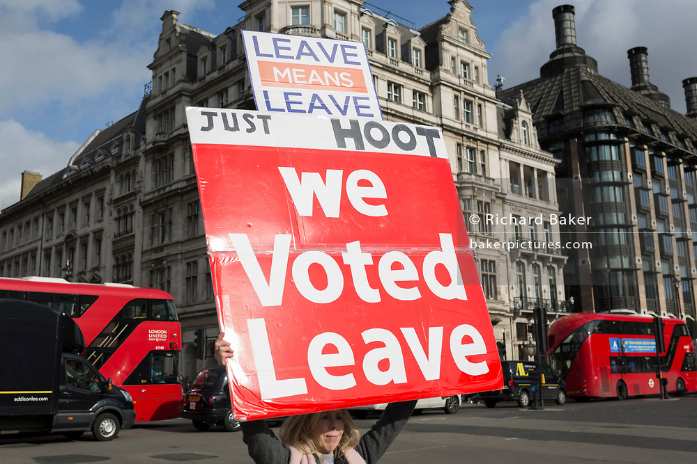 An EU Leave voter holds up a large placard in front of traffic in Parliament Square, on 19th February 2019, in London, England.