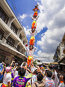 """05 JULY 2014 - BANGKOK, THAILAND: An acrobat team forms a human pyramid on a side street in Bangkok during a parade for vassa. Vassa, called """"phansa"""" in Thai, marks the beginning of the three months long Buddhist rains retreat when monks and novices stay in the temple for periods of intense meditation. Vassa officially starts July 11 but temples across Bangkok are holding events to mark the holiday all week.    PHOTO BY JACK KURTZ"""